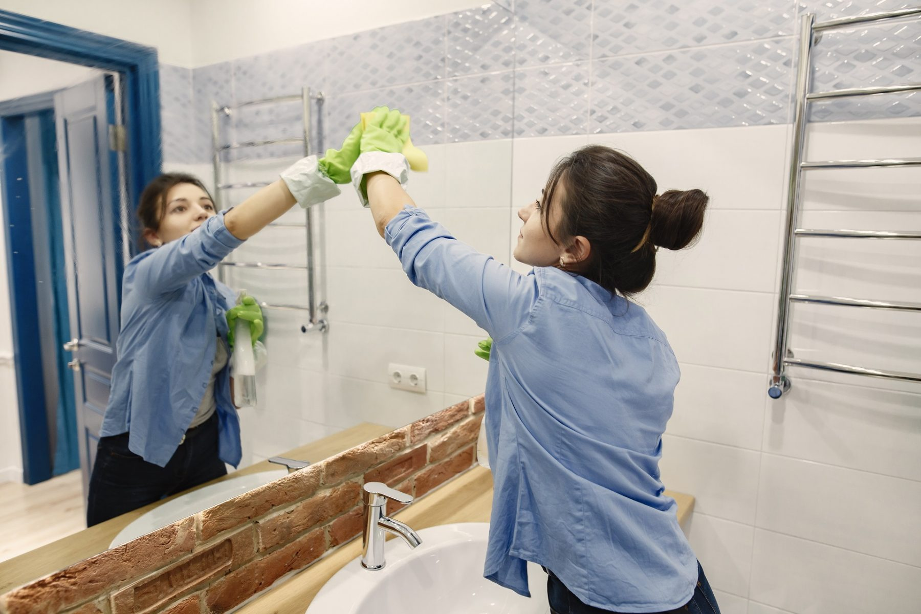 Professional housekeeper cleaning a bathroom in a home